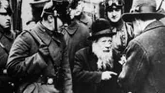 Starého židovského muže šikanují hnědé košile. Antisemitismus dosáhl svého smutného vrcholu pod vládou nacistů.